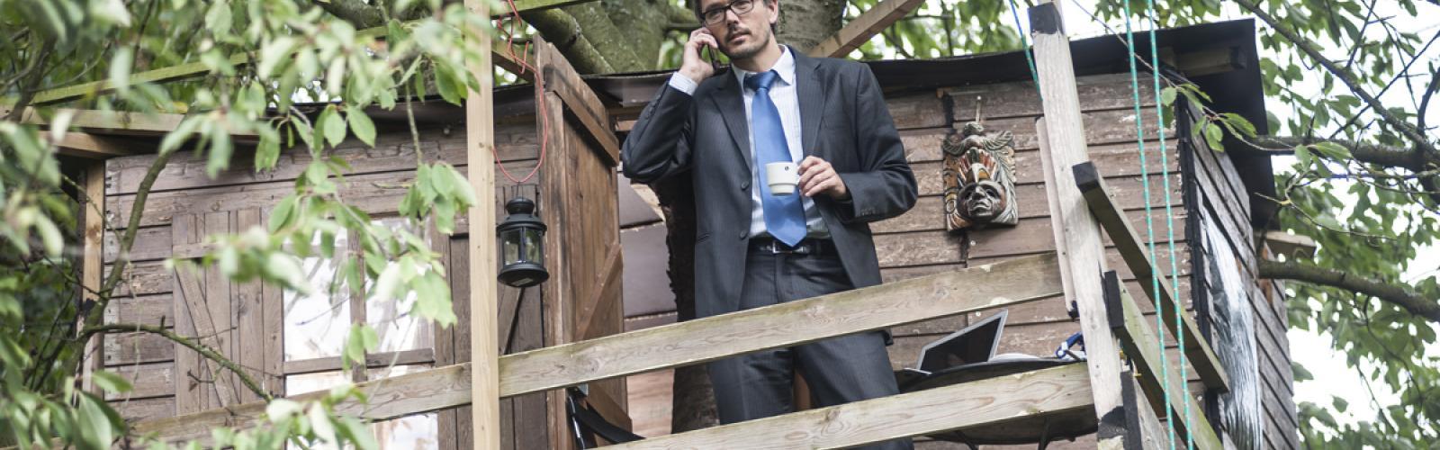 Persoon belt met gsm en drinkt koffie in een boomhut