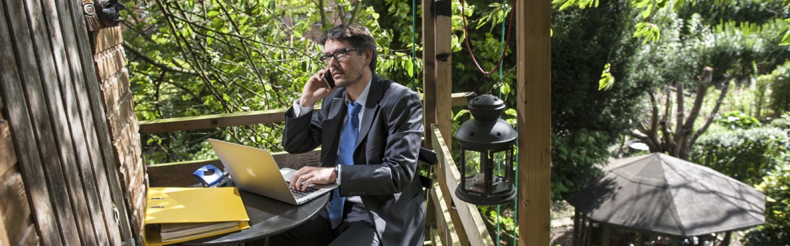 Persoon werkt op laptop en belt met gsm in een boomhut in groene omgeving
