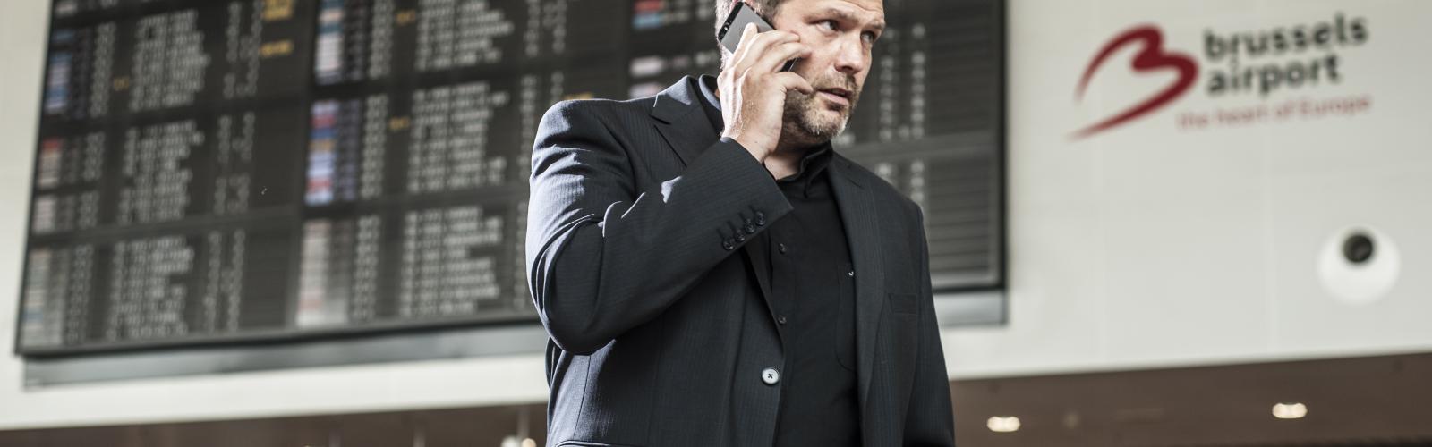 Man telefoneert op de luchthaven