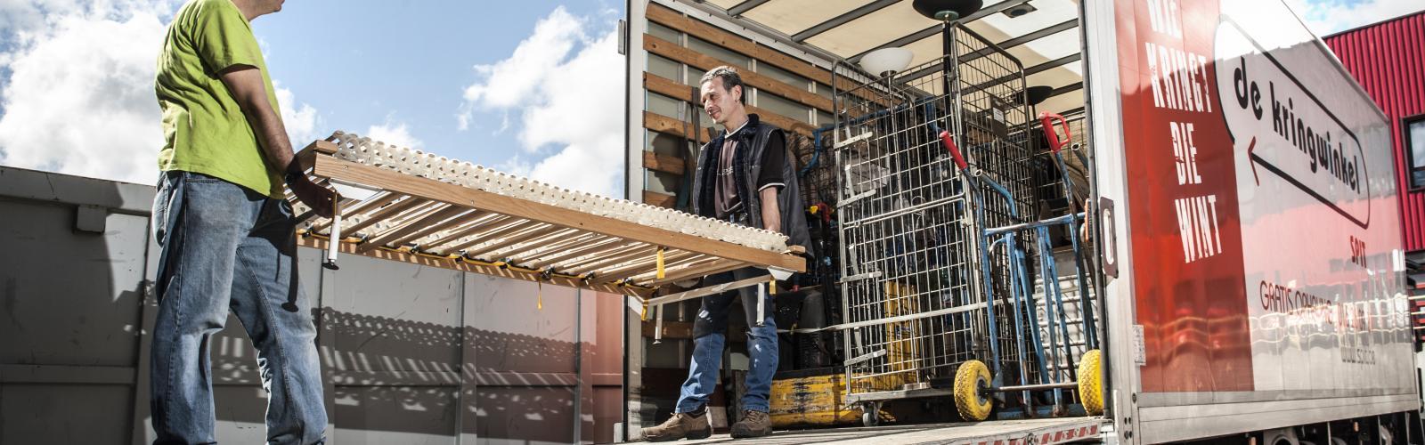 Mensen van de kringloopwinkel lossen hun opgehaalde goederen