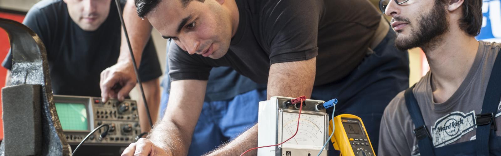 werknemer test spanning op een machine en andere collega's kijken geboeid toe