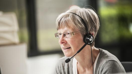 Vrouw helpt mensen verder aan de telefoon