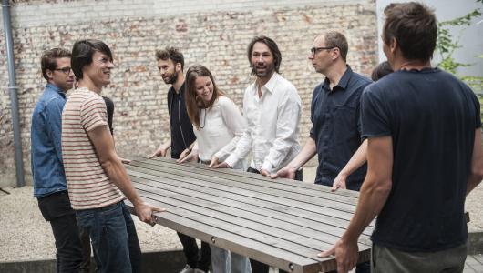 groep mensen dragen samen een tafel