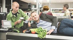 Ondernemer ligt op de band van de kassa van de supermarkt en wordt gescand door de kassier